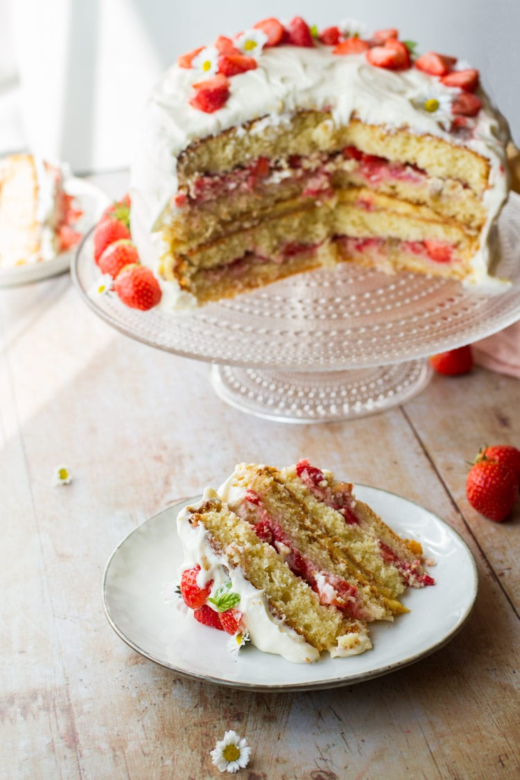 Strawberry cake slice with the whole strawberry cake in the background.