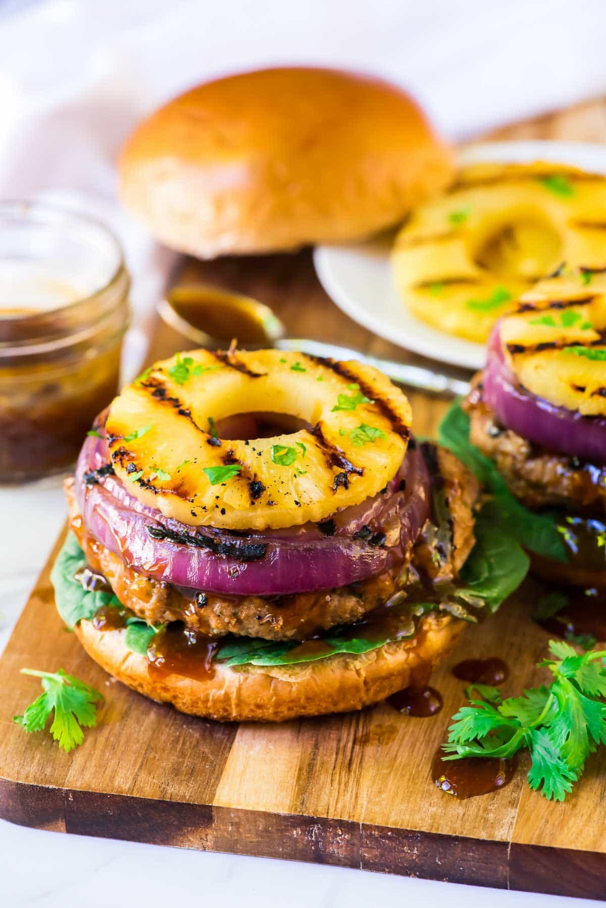 Teriyaki burger with red onion slices and grilled pineapple.