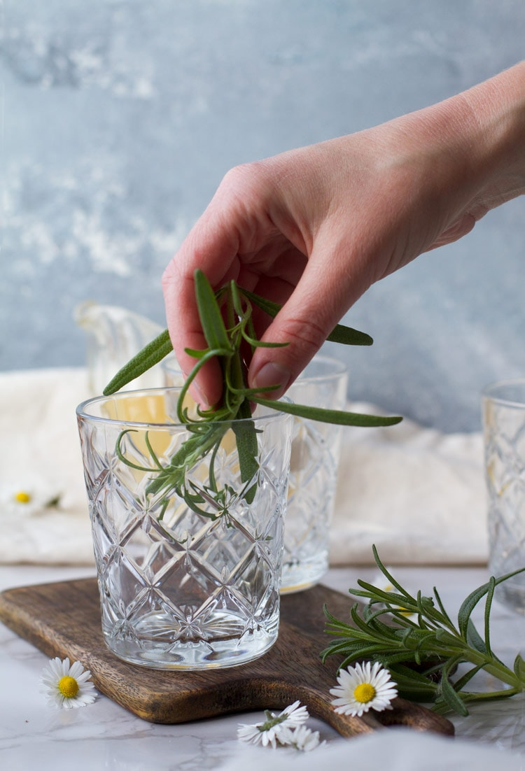 Rimming glass with fresh rosemary.