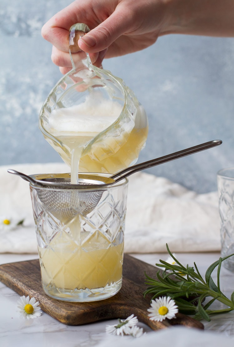 Pouring finished apricot rosemary gin fizz into a strain and glass.