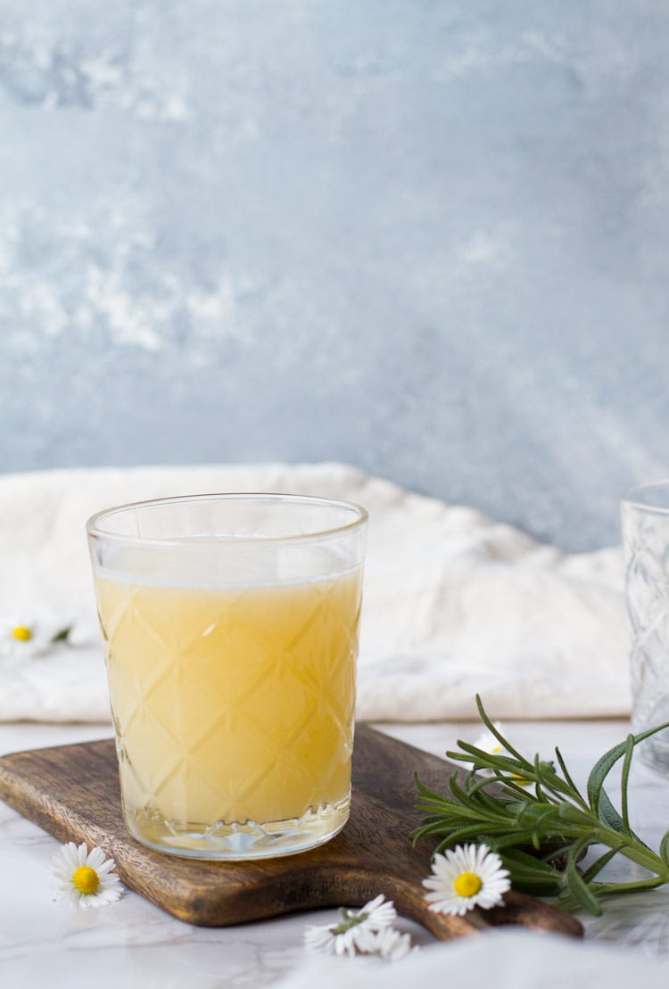 Apricot Rosemary Gin Fizz on a cutting board, blue background.