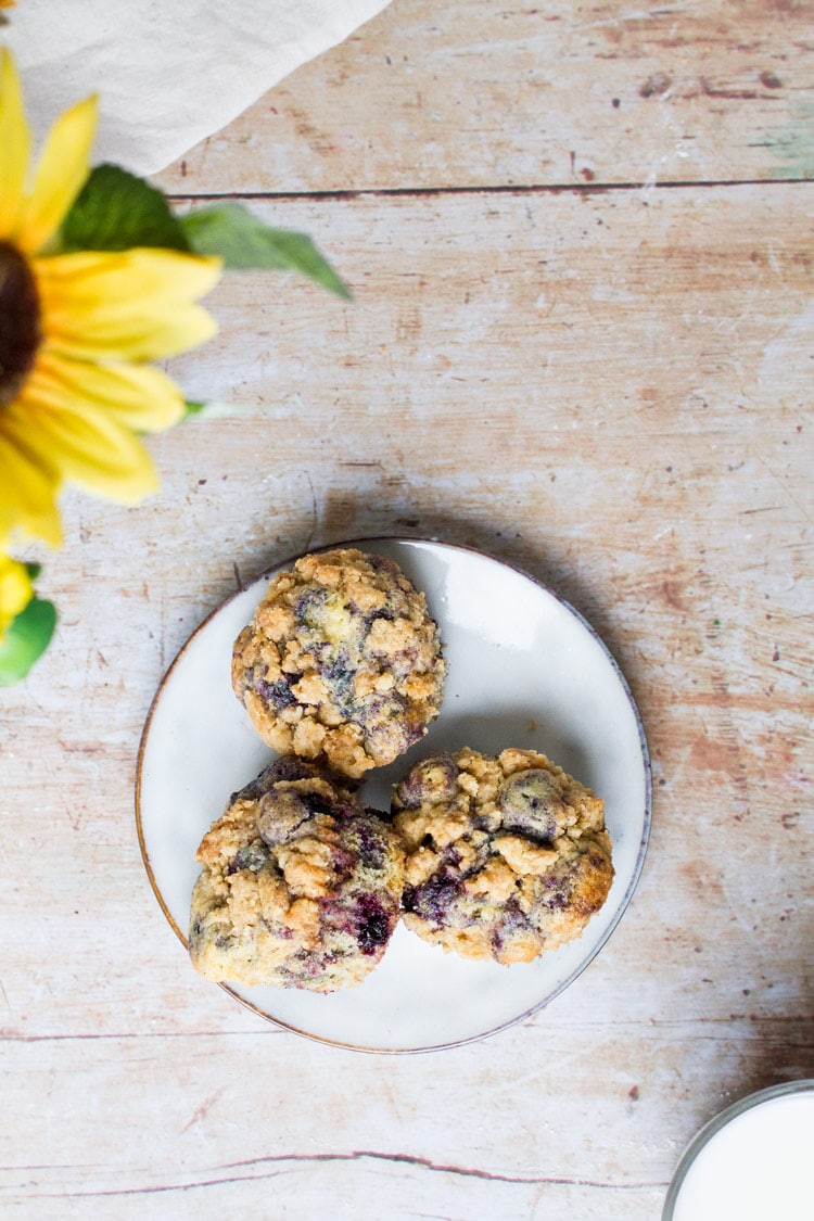 Three homemade blueberry muffins on a white plate. Wooden background and sunflowers in the upper left corner.