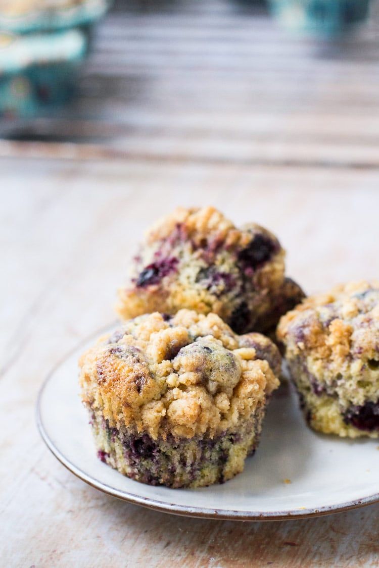 Three homemade blueberry muffins on a white plate.