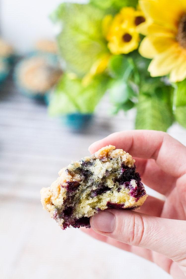 Hand holding an open homemade blueberry muffin.