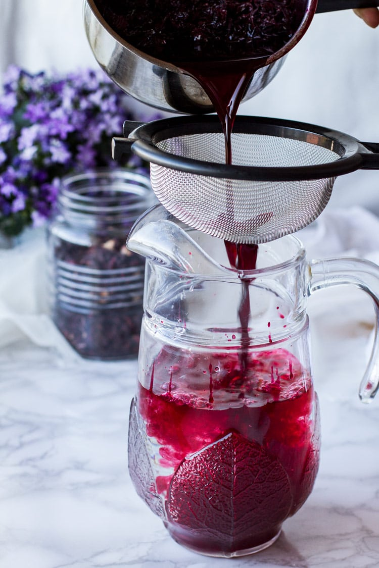 Pouring hibiscus syrup into a sieve and mug.