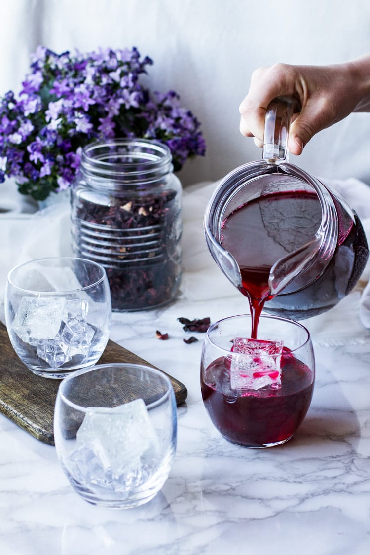 Pouring hibiscus tea into one of three glasses. Dried hibiscus in a mason jar in the background.