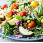 Healthy pasta salad on a dark plate, jar with pasta dressing in the background. Pinterest pin.