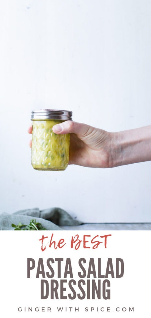 Hand holding a glass jar with a healthy pasta salad dressing. Pinterest pin.