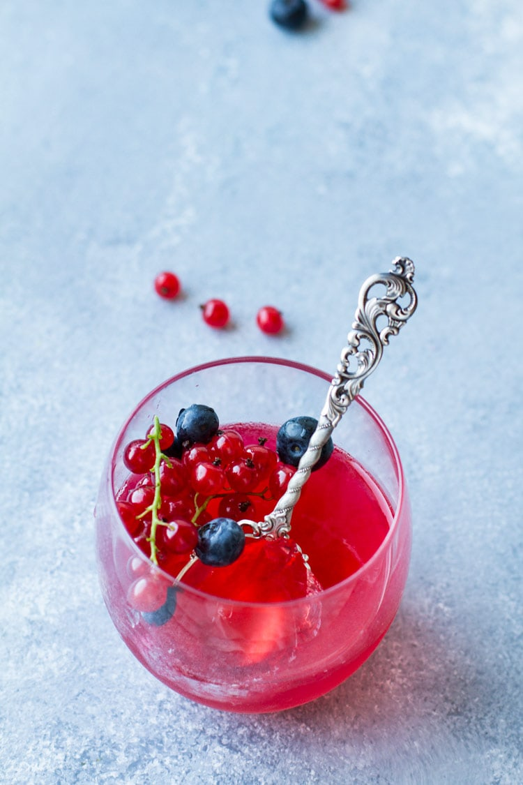 One glass with homemade jello recipe, berries and a vintage spoon.