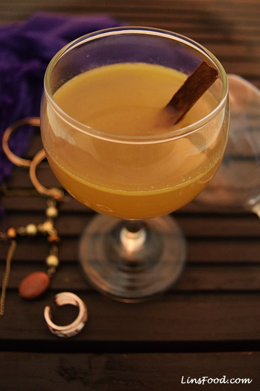 Hot Buttered Brandy drink with cinnamon stick in a wine glass.