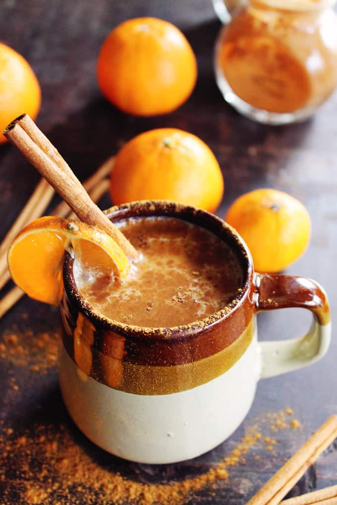 Almond Milk Chai Hot Drink in a white and brown cup, garnished with oranges and cinnamon stick.