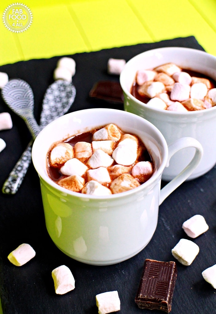 Boozy hot chocolate drink with marshmallows in a white cup.