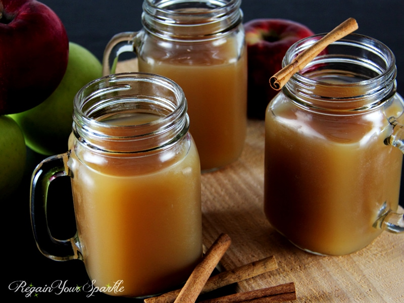 Hot Drink with Apple pie flavor in mason jars, cinnamon stick on the table.