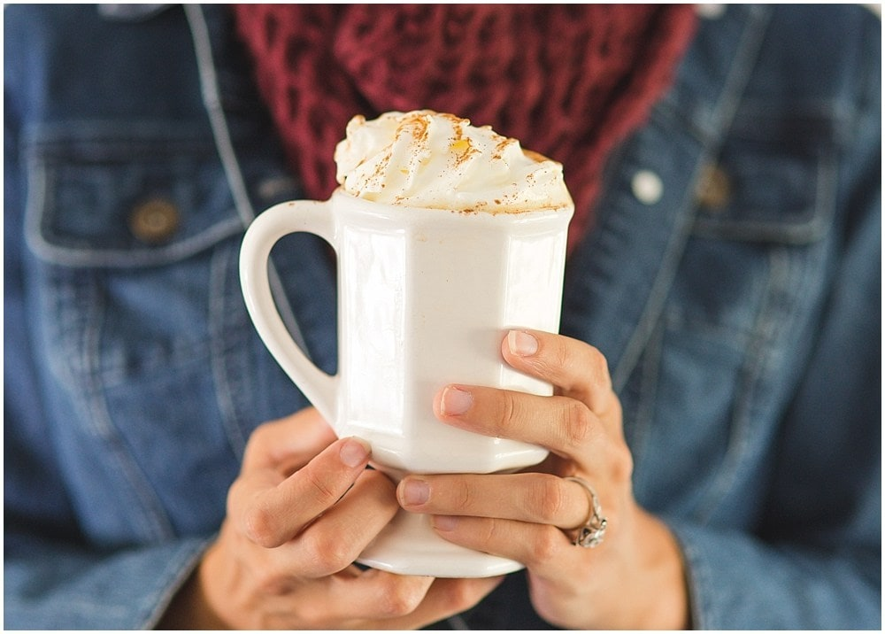 Hands holding a white cup with hot maple pecan latte and whipped cream. Red scarf.