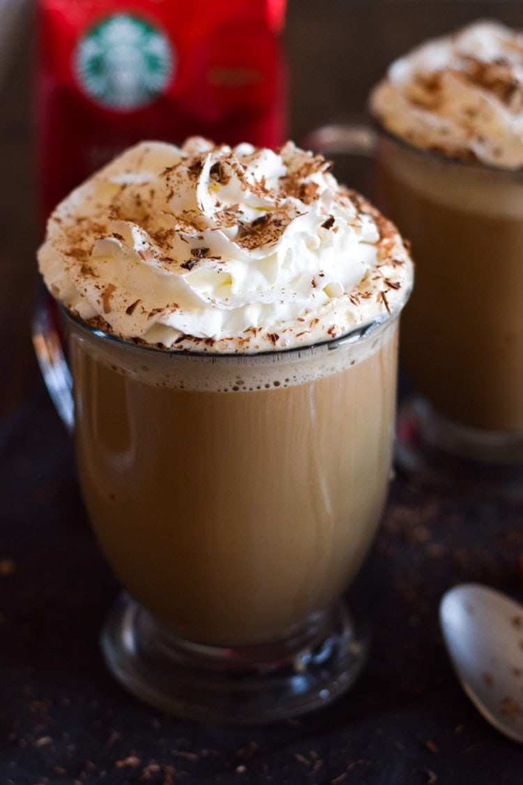 Mexican tres leches coffee in a clear cup, topped with whipped cream.