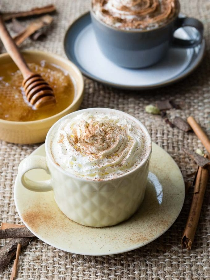 Hot Drink with milk and honey in a white cup. Honey in the background.