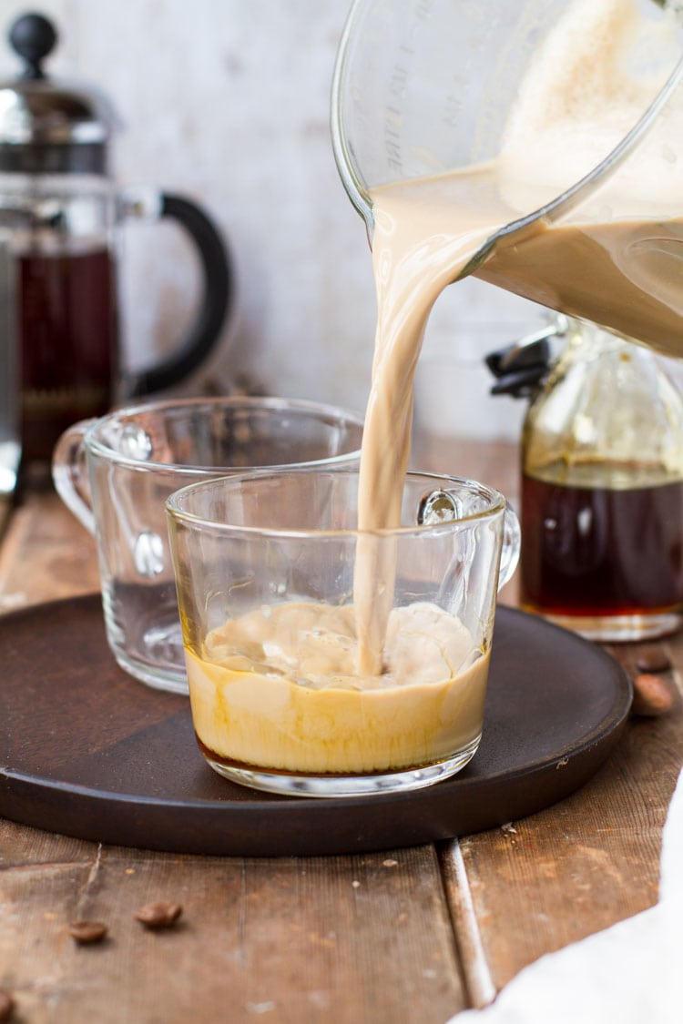 Pouring apple caramel latte macchiato from blender to glass cup.