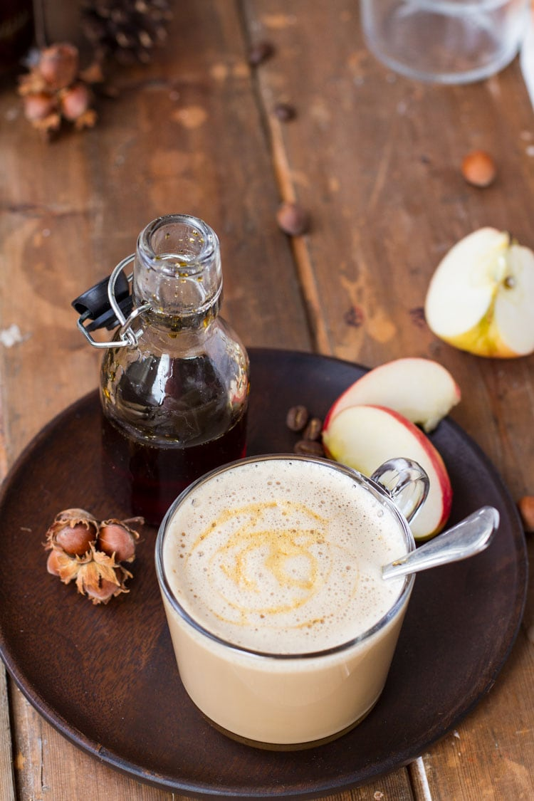 A clear mug with apple caramel latte macchiato. Glass jar with caramel sauce and apple slices on wooden plate.