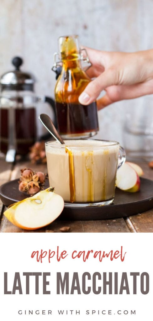 Glass cup with apple caramel latte macchiato, drizzle with caramel on the edges, hand holding glass jar with caramel in the background. Pinterest pin.