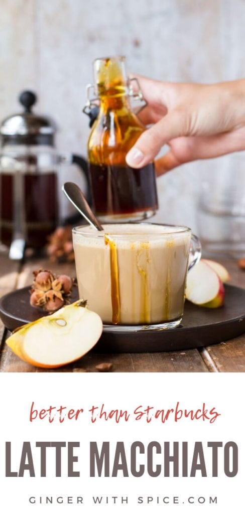 Glass cup with apple caramel latte macchiato, drizzle with caramel on the edges, hand holding glass jar with caramel in the background. Pinterest pin #2.