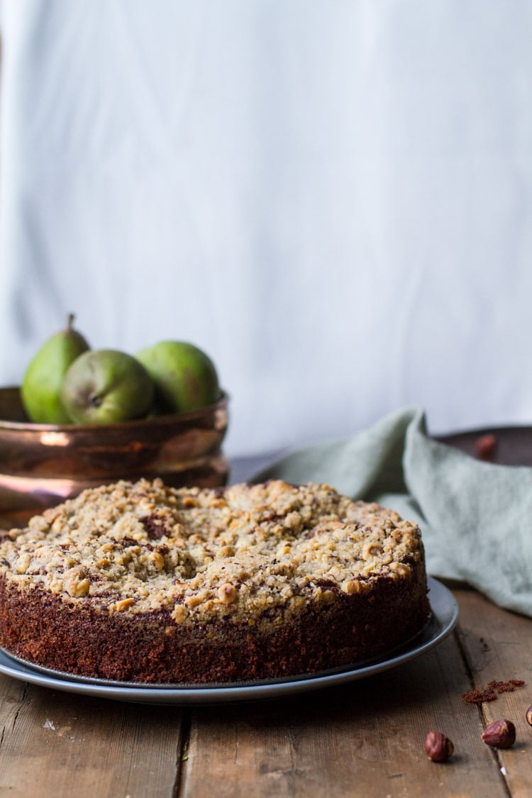 Chocolate Pear Cake with crumb topping on a dark plate, pears in the background.