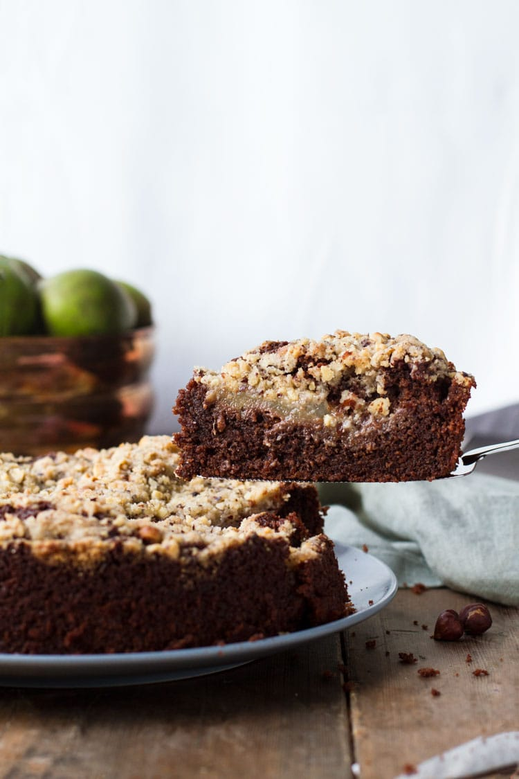 Taking a slice of chocolate pear cake out of the whole cake.