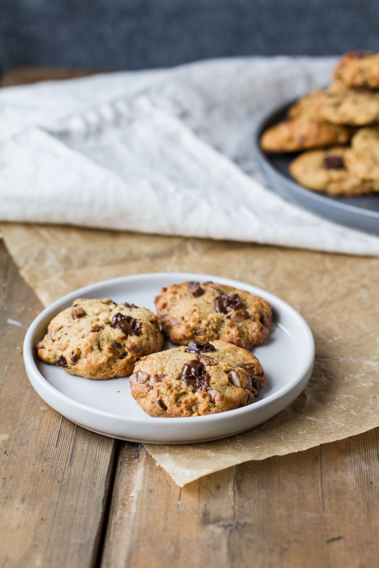 Plate with three chocolate chip cookies on a parchment paper.