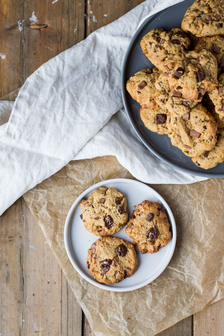 Three peanut butter chocolate chip cookies on a white plate on parchment paper and wooden table.