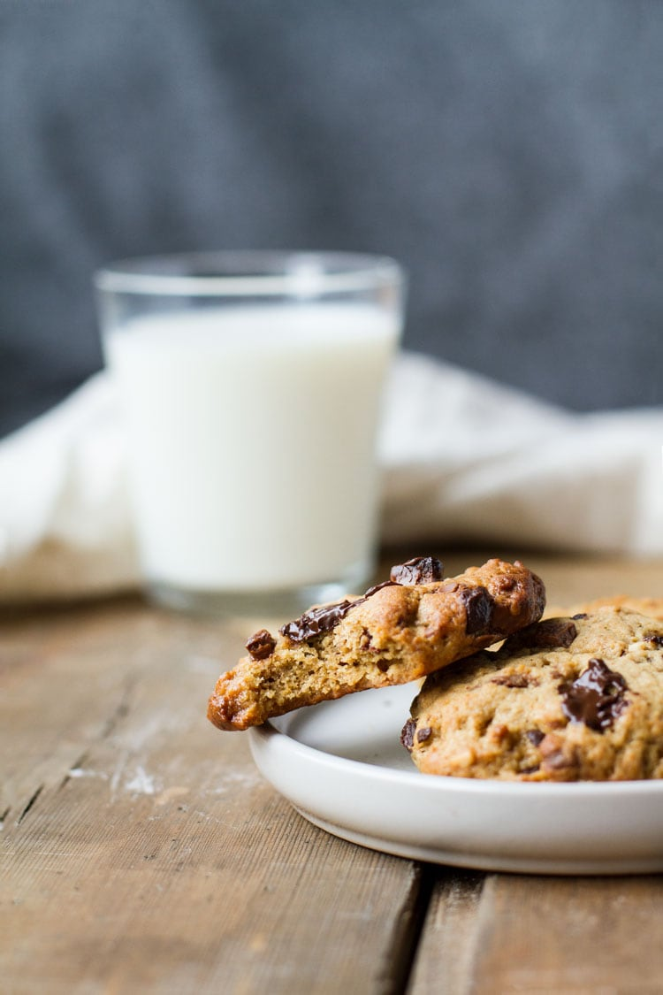 One chocolate chip cookie taken a bite out of, milk in the background.