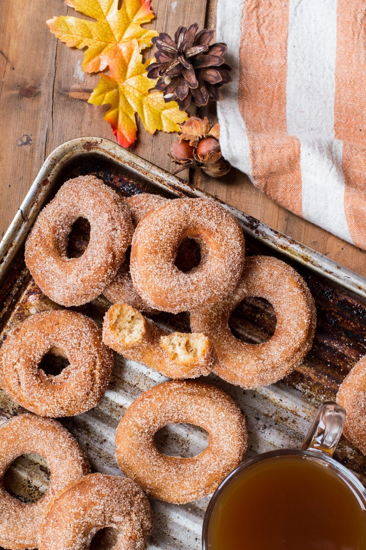 Apple Cider Donuts and a cup of apple cider on a metal pan. One taken a bite out of.