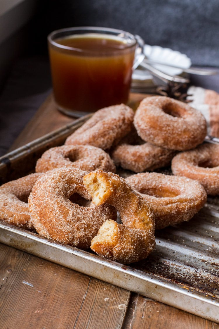 Apple cider donuts, one taken a bite out of, on a metal pan. Clear cup of apple cider in the background.