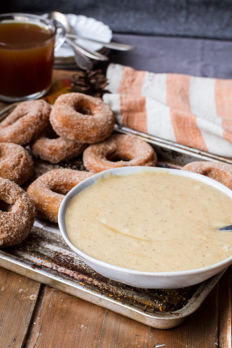 Brown butter cinnamon glazing in a bowl, with donuts in the background.