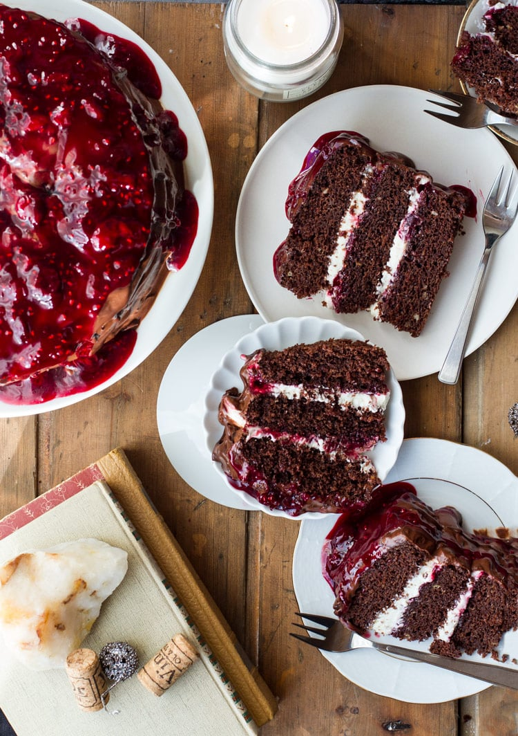 Three white plates with slices of black forest cake and the whole cake in the upper left corner.
