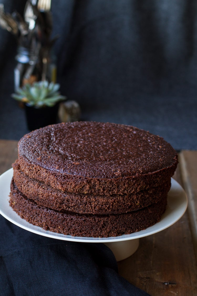Three chocolate sponge cakes on top of each other on a white plate.