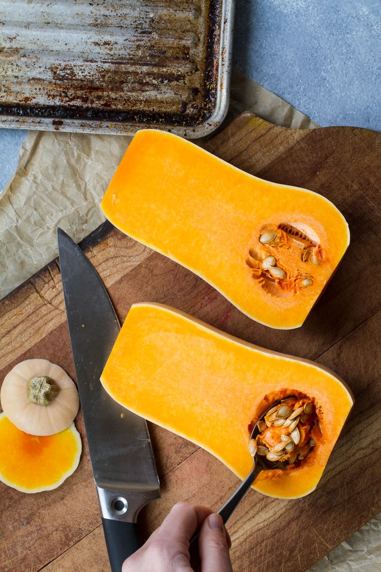 Scooping out pumpkin seeds out of halved butternut squash.