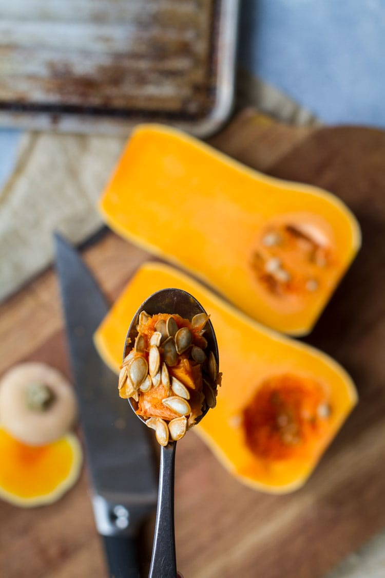 Spoon with pumpkin seeds and strings in focus, butternut squash out of focus in the background.