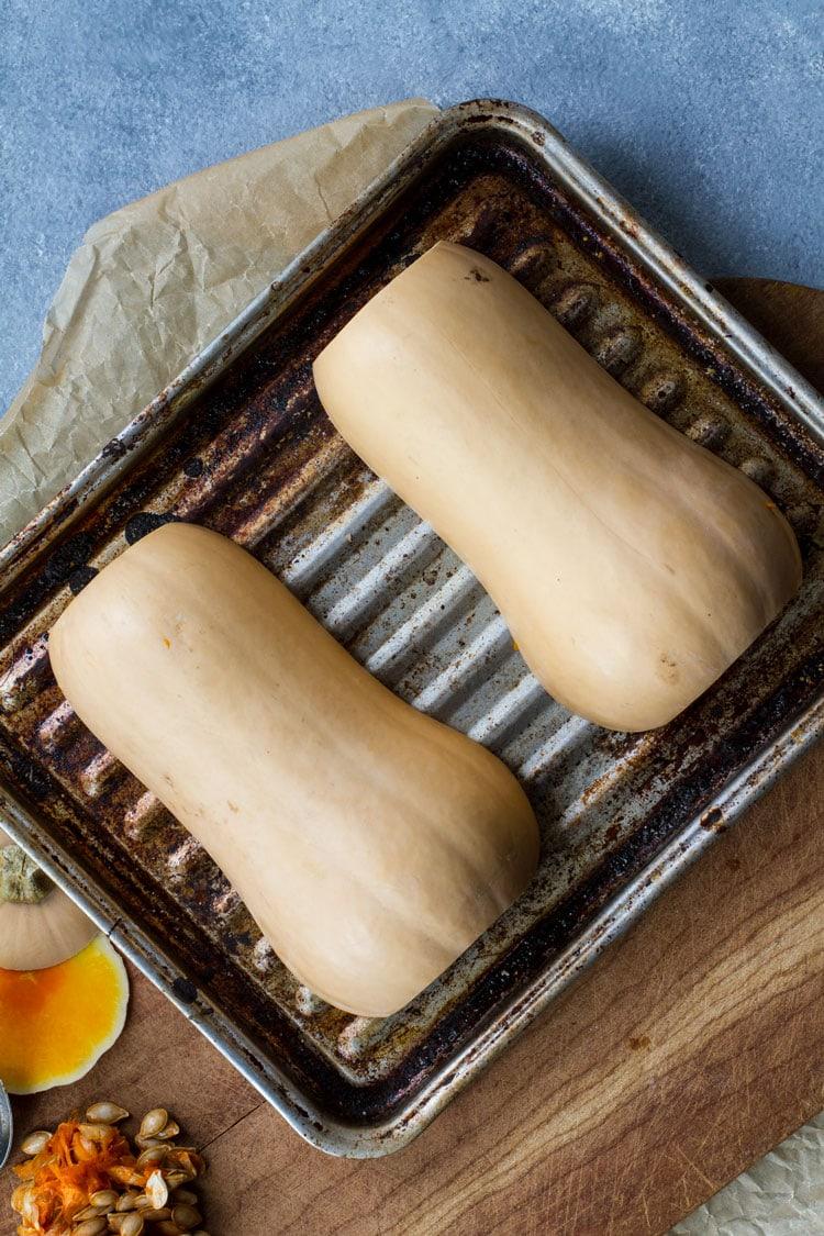 Halved butternut squash on a vintage baking sheet.