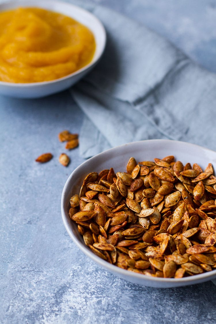 Bowl of roasted pumpkin seeds on a blue table.