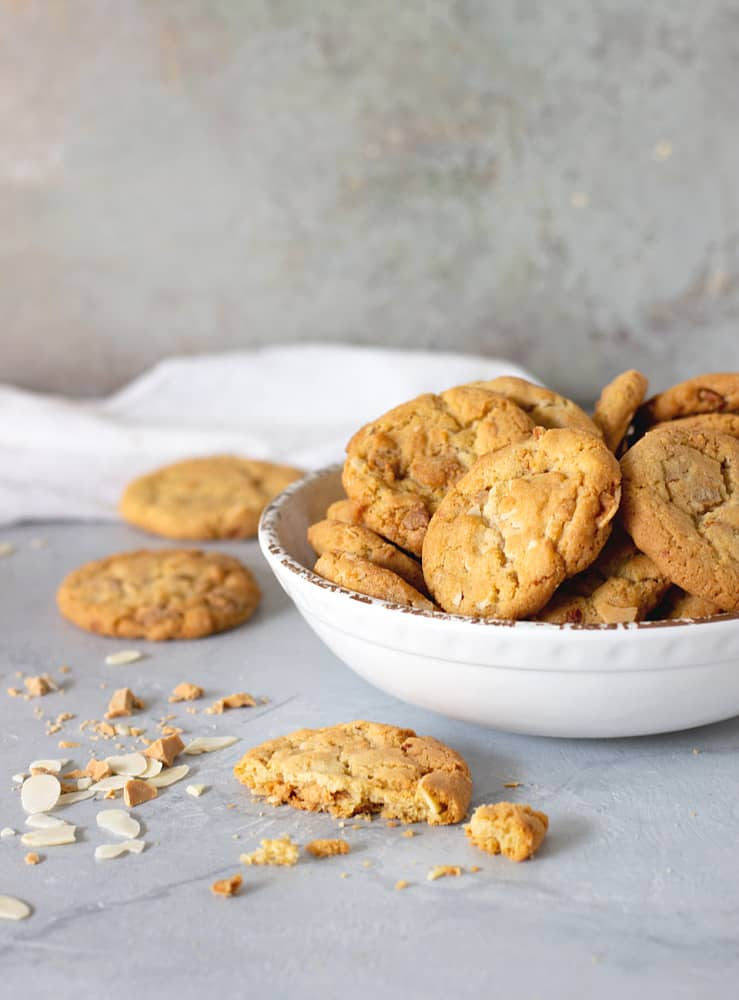 Cookies in a white bowl. One open on the table.