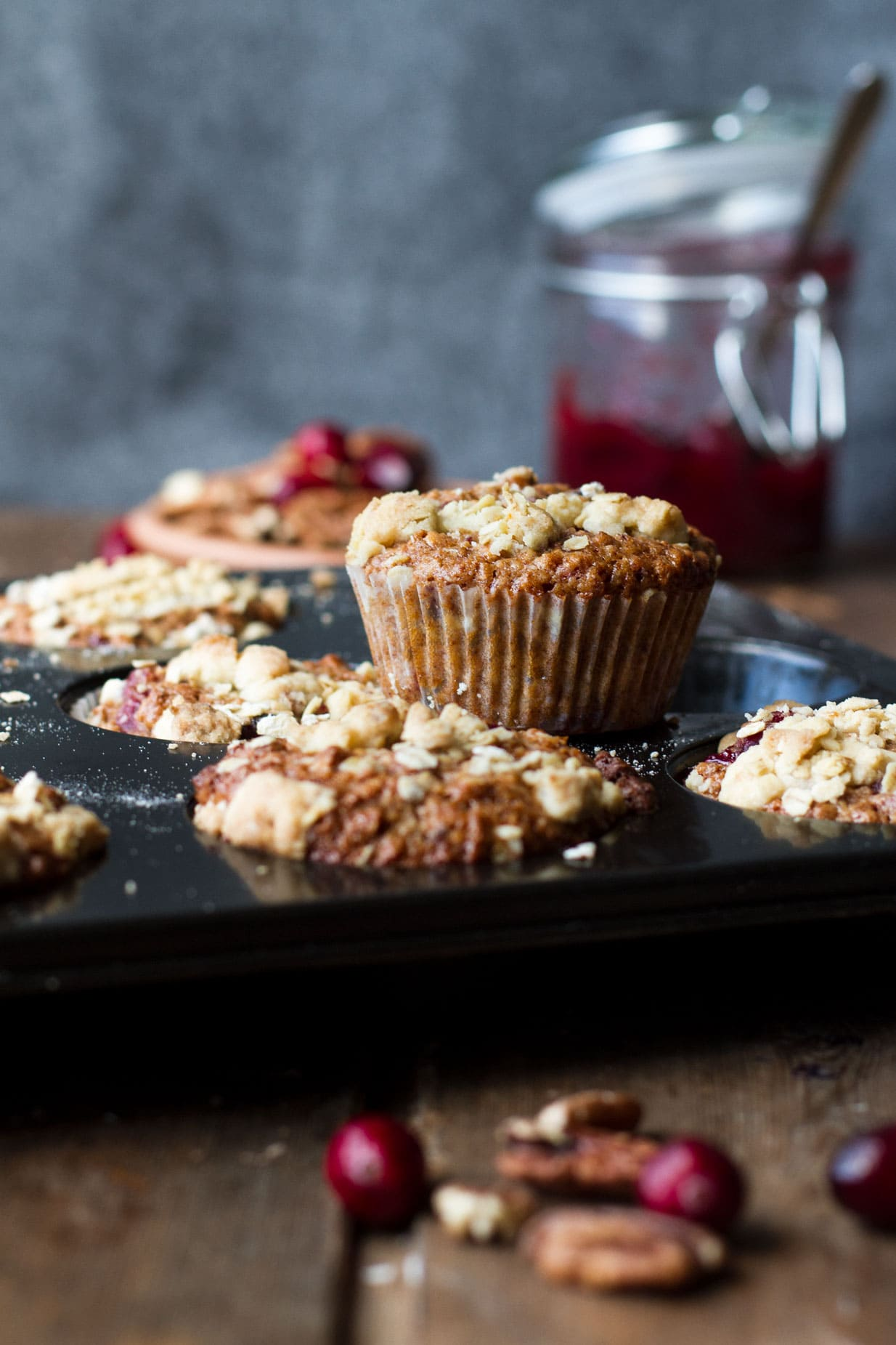 A muffin tin with cranberry sauce breakfast muffins, one standing on top of the tin.