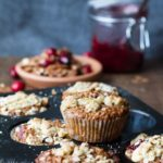 Cranberry sauce breakfast muffins on a muffin tin. Cranberry sauce in the background.