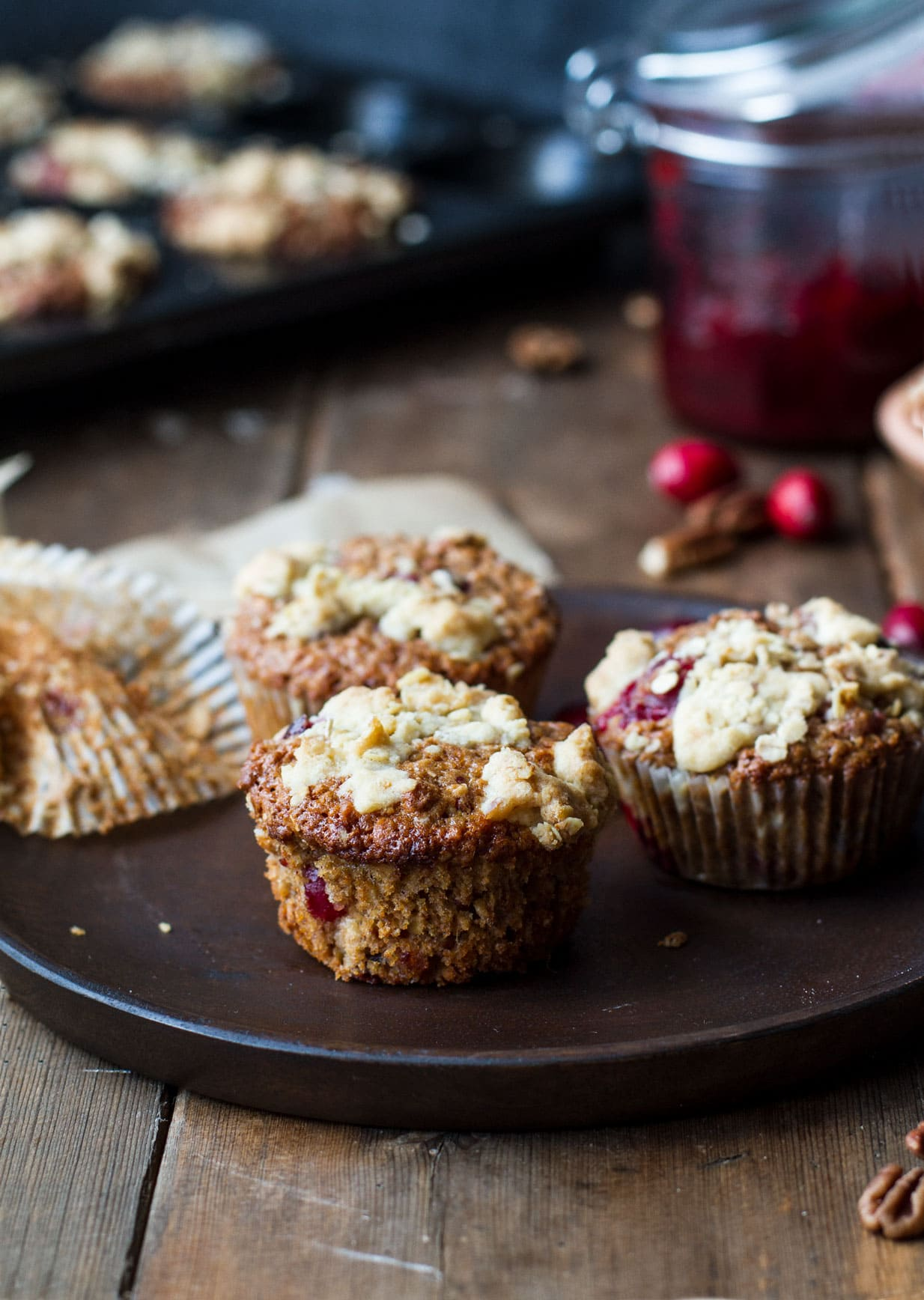 Three cranberry sauce oat breakfast muffins on a wooden plate.