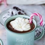 Mint colored enamel mug with mocha coffee, whipped cream and candy cane garnish.