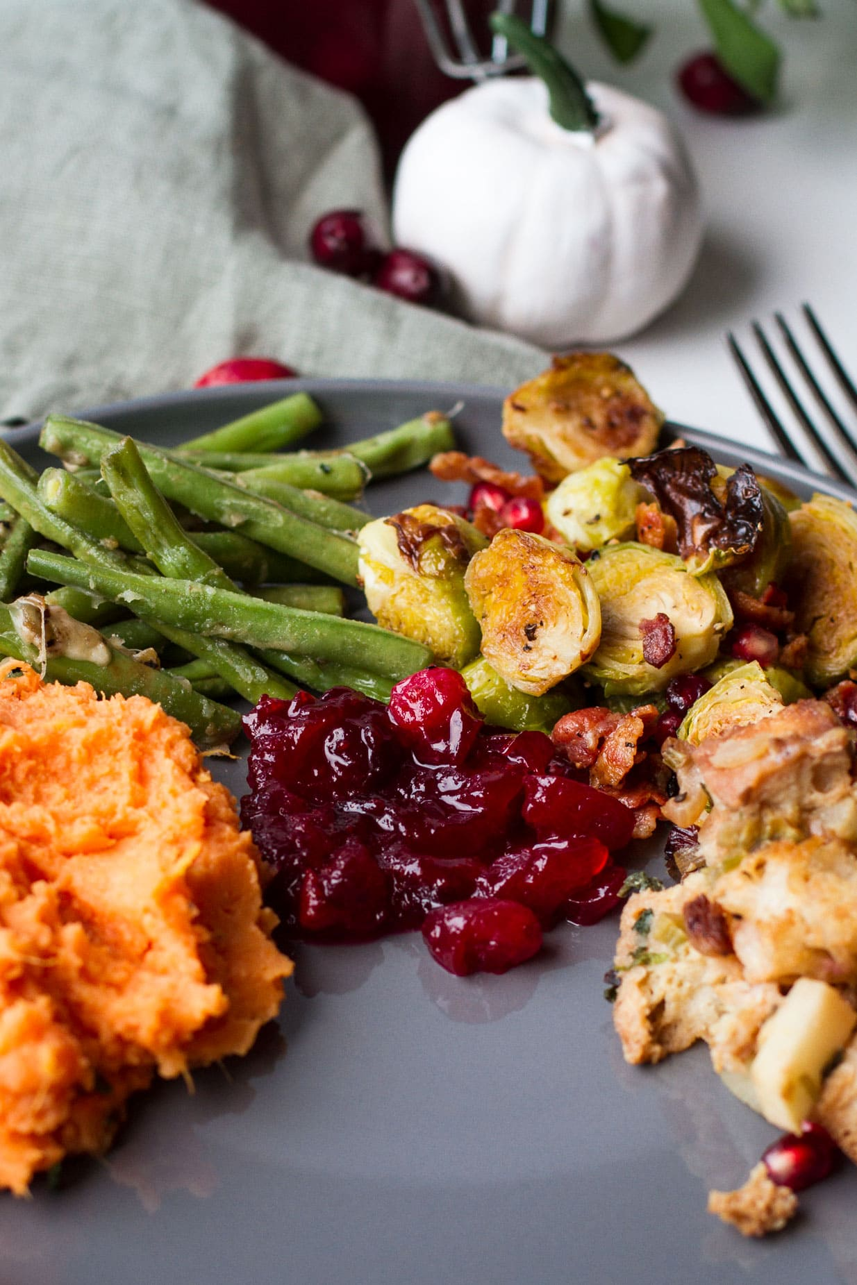 Thanksgiving side dishes; green beans, cranberry sauce, stuffing, sweet potato mash, brussels sprouts.