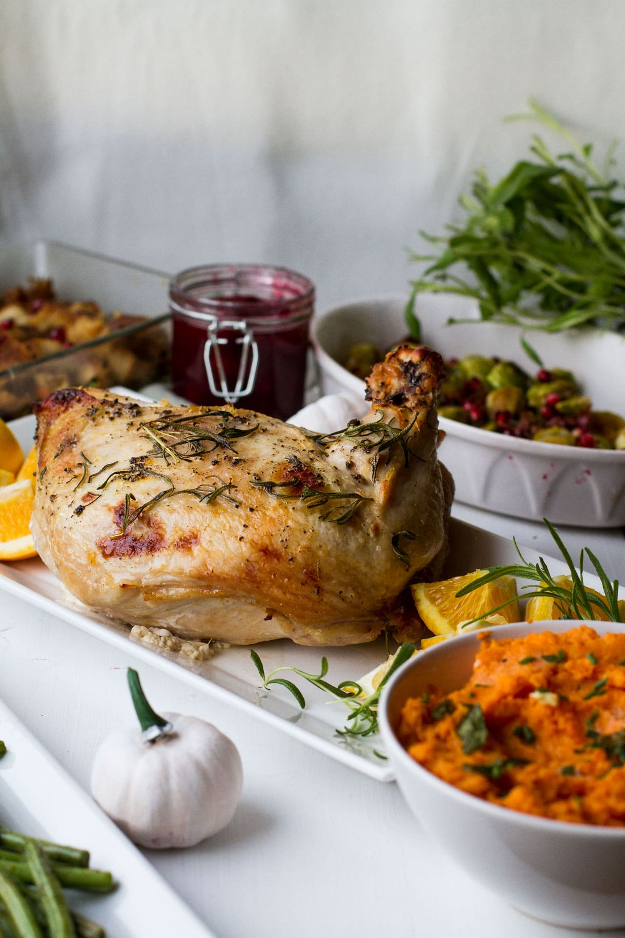 Turkey breast on a white plate, Thanksgiving side dishes around.