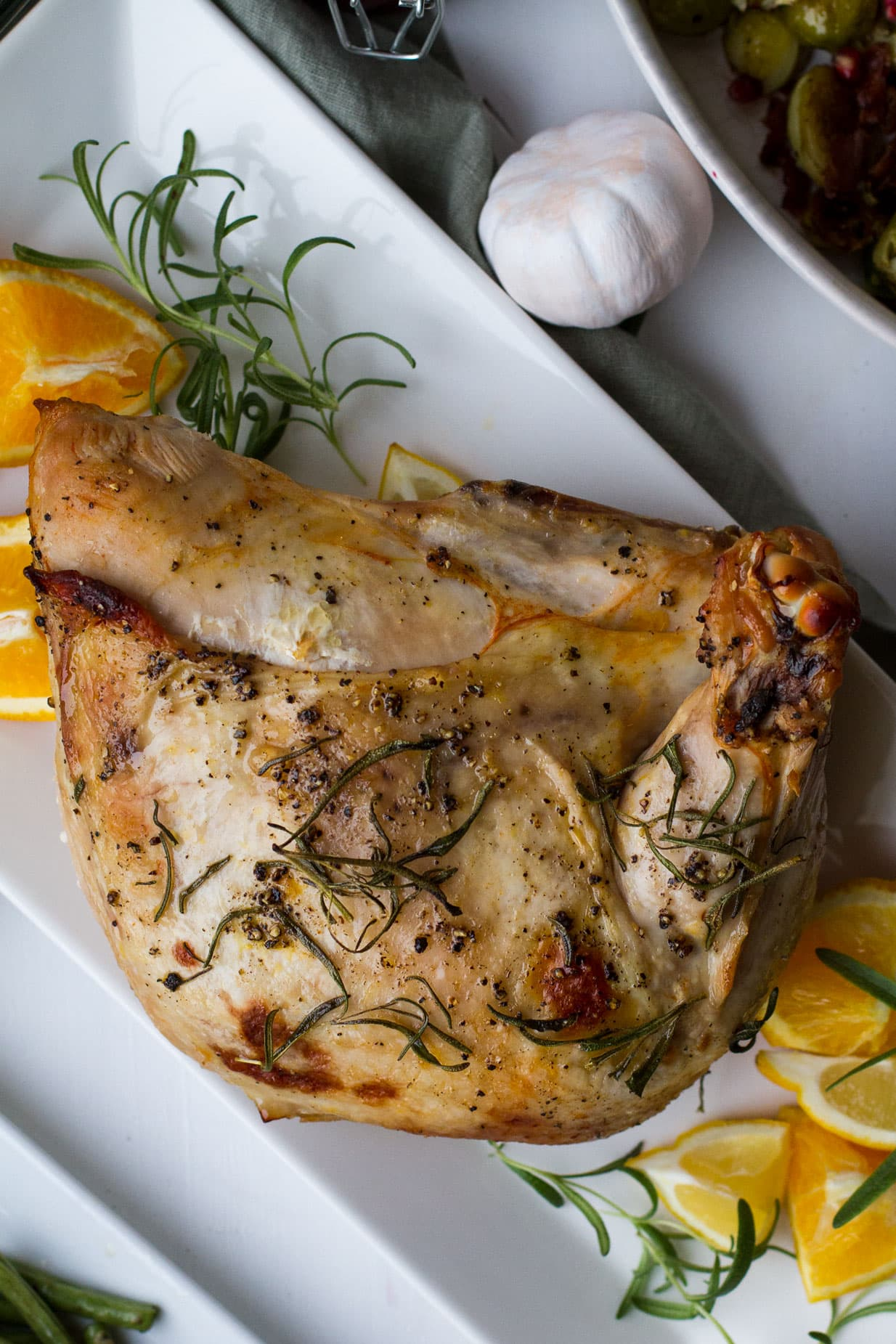 Turkey breast on a plate, garnished with orange quarters and rosemary sprigs.