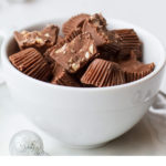 Almond Crunch Milk Chocolates, a few cut open, in a small white cup. Pinterest pin.