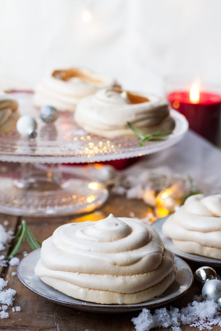 Christmas Pavlova Dessert with eggnog whipped cream. More on a cake stand in the background.