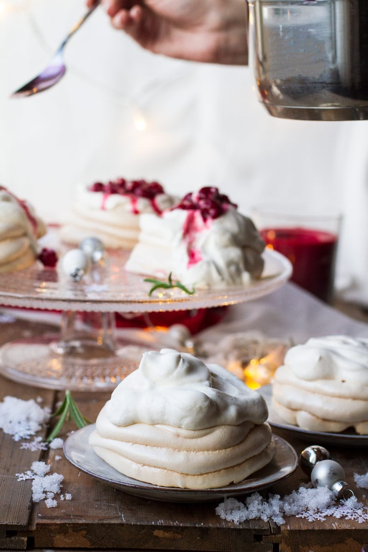 Pouring cherry sauce on a Christmas Pavlova Dessert in the background, the foreground is without sauce.