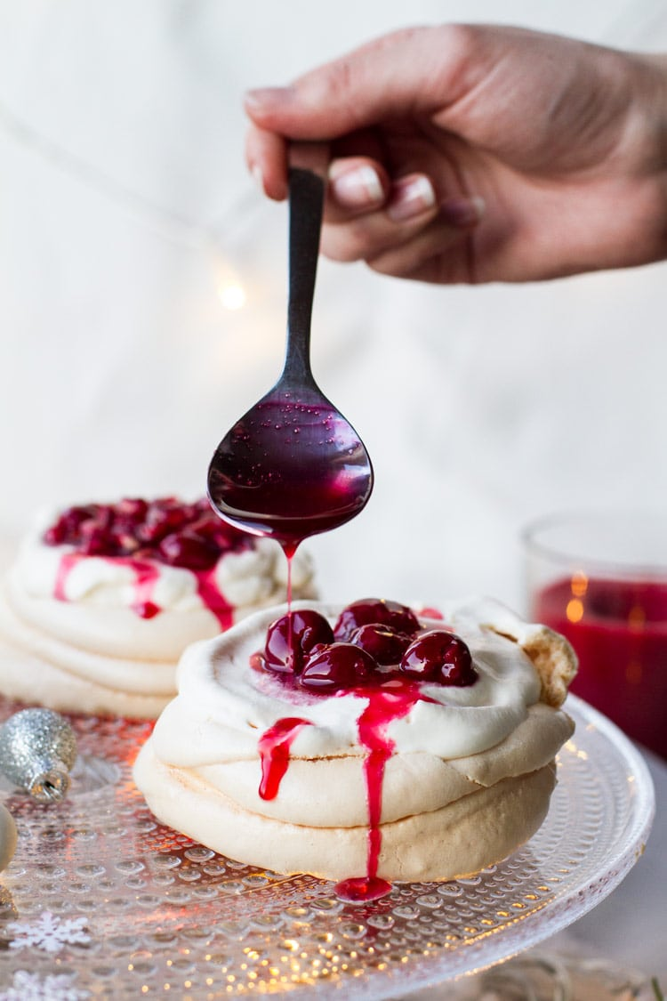 Pouring cherry sauce on a Christmas Pavlova Dessert with eggnog whipped cream.
